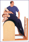 A man assisting a woman to balance and deepen her side stretch.